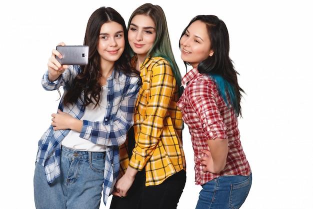 Três modelos de meninas felizes fazem selfie sorrindo isolado no branco