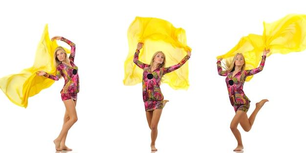 Três modelos de mulheres bonitas loiras jovens isoladas em um vestido rosa com padrão oriental dançando com um pano de seda amarelo sobre um fundo branco no estúdio fotográfico. conceito de estilo de vida de moda e beleza