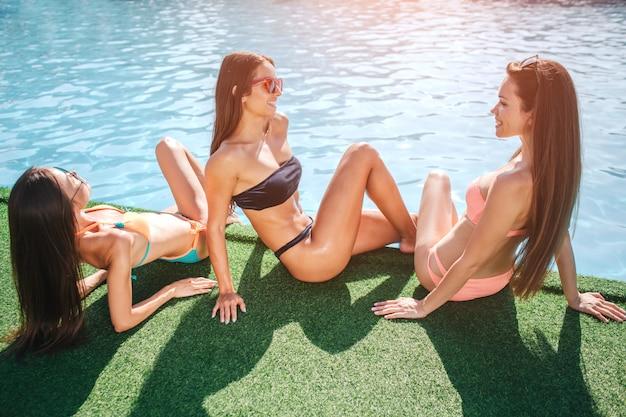 Três modelos deliciosos estão sentados na grama, na beira da piscina. um fica bronzeado pelo sol. os outros dois se entreolham e sorriem. mulheres jovens se divertem. eles relaxam.