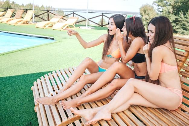 Três modelos sentam-se em espreguiçadeiras. dois deles estão fofocando. mulher à esquerda aponta para a frente. o modelo no meio está inclinado para o primeiro. eles descansam.