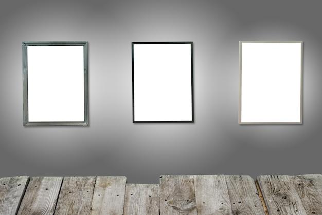 Três molduras de madeira isoladas brancas na parede cinza com mesa de madeira