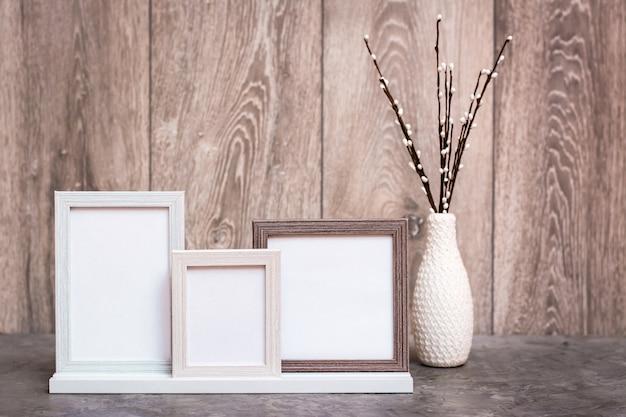 Três molduras vazias no suporte e um vaso com galhos de salgueiro artificiais estão sobre a mesa. gama de cores branco-cinza-bege. copie o espaço