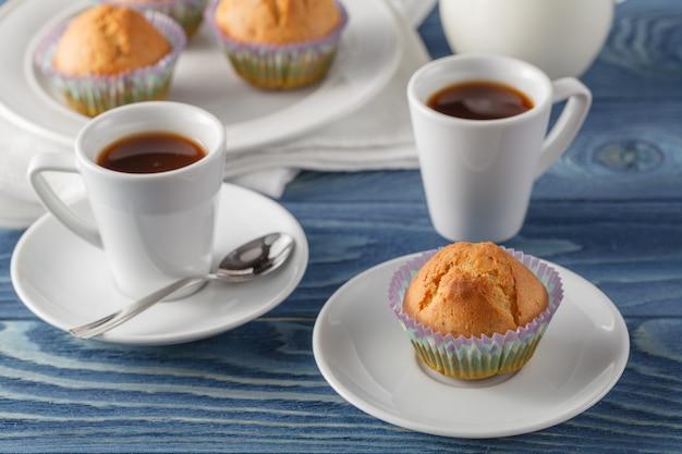 Três muffins de chocolate na chapa branca e toalha de mesa às riscas azuis no café da manhã