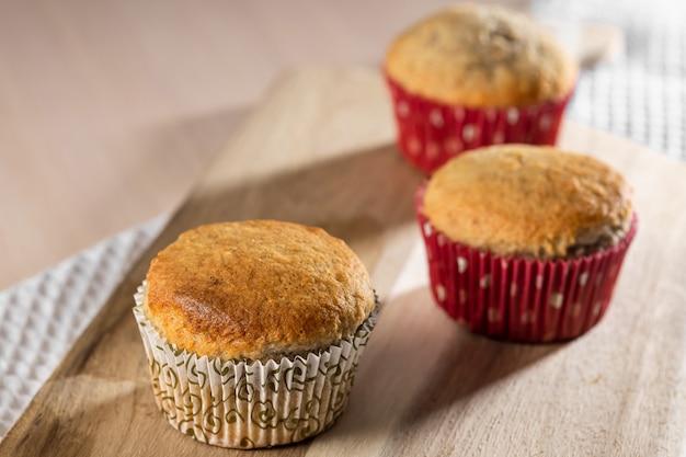 Três muffins saborosos caseiros na placa de madeira close-up