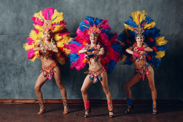 Três mulher dançando em traje de carnaval de samba brasileiro com plumagem de penas coloridas.