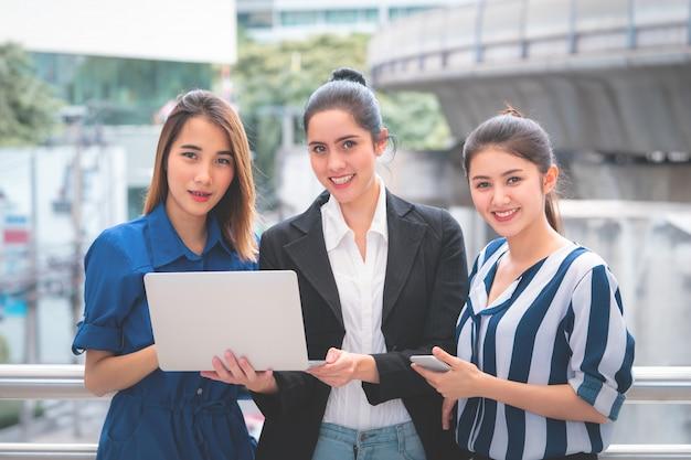 Três, mulher negócio, segurando, laptop