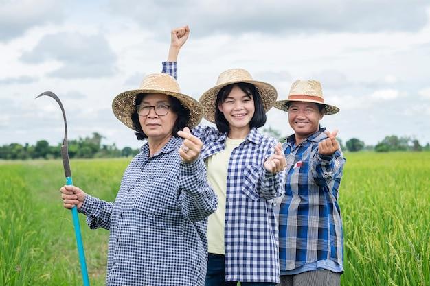 Três mulheres agricultoras asiáticas posam mãos em miniatura e sorriem para uma fazenda verde
