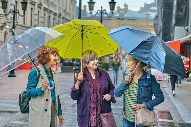 Três mulheres alegres de meia-idade com guarda-chuvas coloridos caminham pelo centro da cidade durante a chuva.
