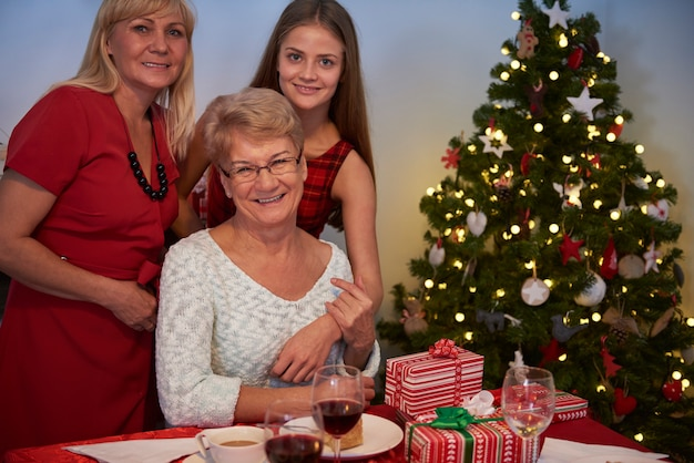 Três mulheres ao lado da árvore de natal