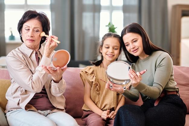 Três mulheres aplicando maquiagem enquanto estão sentadas no sofá da sala de estar