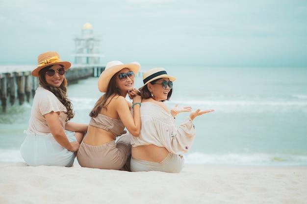 Três mulheres asiáticas sentada na praia de férias com a emoção da felicidade