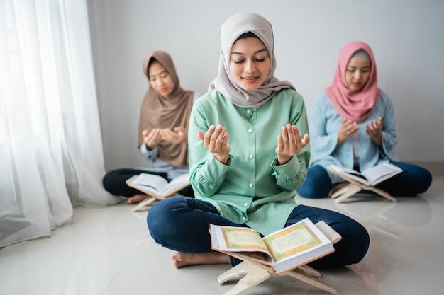 Três mulheres asiáticas sentam e oram para dar graças a deus