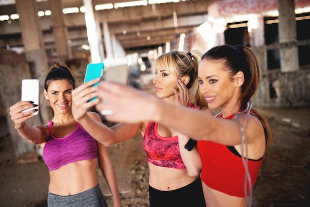Três mulheres atraentes em forma estão fazendo uma selfie em local abandonado.