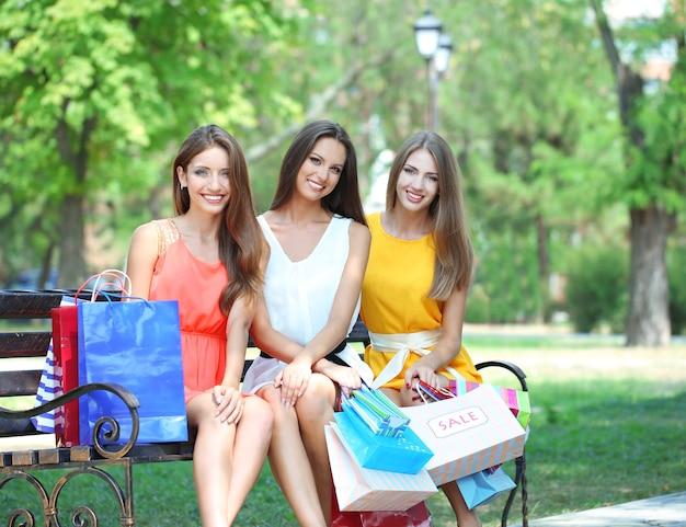 Três mulheres bonitas com sacolas de compras no parque