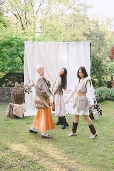 Três mulheres bonitas em pé no jardim.