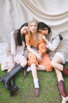 Três mulheres bonitas, sentado no chão e olhando no jardim.