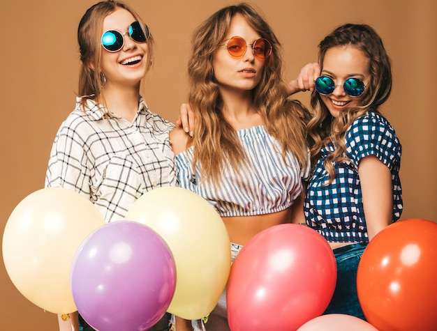Três mulheres bonitas sorridentes em roupas de verão camisa quadriculada e óculos de sol. meninas posando. modelos com balões coloridos. se divertindo, pronto para comemorar aniversário