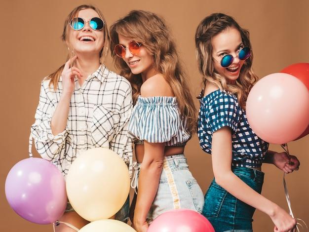Três mulheres bonitas sorridentes em roupas de verão camisa quadriculada. meninas posando. modelos com balões coloridos em óculos de sol. se divertindo, pronto para comemorar aniversário