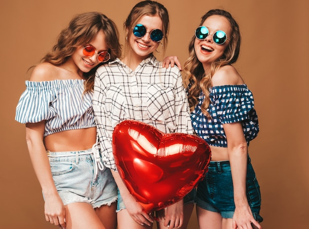 Três mulheres bonitas sorridentes em roupas de verão camisa quadriculada. meninas posando. modelos com forma de coração vermelho balão em óculos de sol. pronto para a celebração do dia dos namorados
