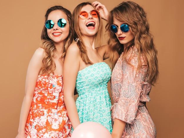 Três mulheres bonitas sorridentes em vestidos de verão. meninas posando. modelos com balões coloridos. se divertindo, pronto para comemorar aniversário ou festa natalícia