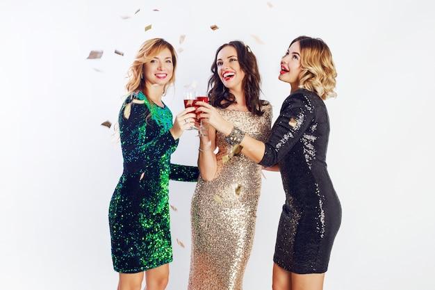 Três mulheres celebrando com roupas brilhantes para a noite, curtindo o tempo juntas, bebendo vinho e dançando
