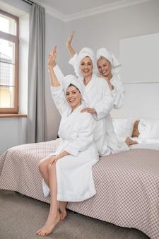Três mulheres com as mãos levantadas na cama
