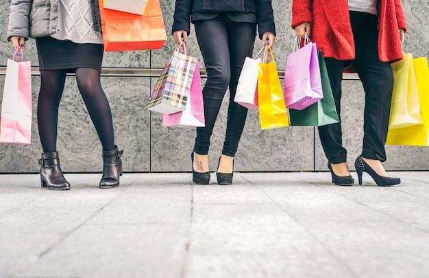 Três mulheres com muitas sacolas de compras