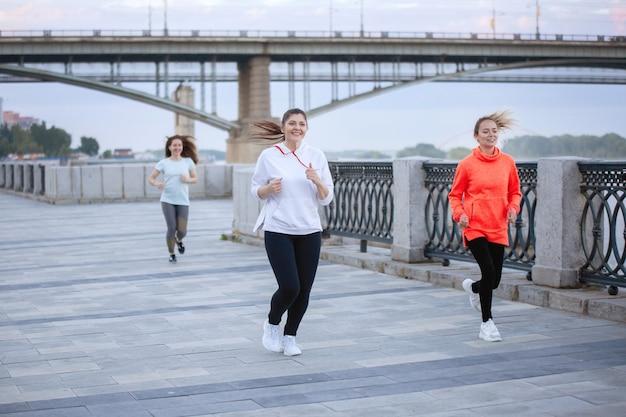 Três mulheres correm pela calçada em uma sessão de treinamento em uma rua da cidade no verão.