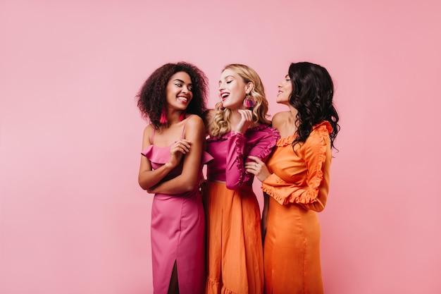 Três mulheres dançando na parede rosa