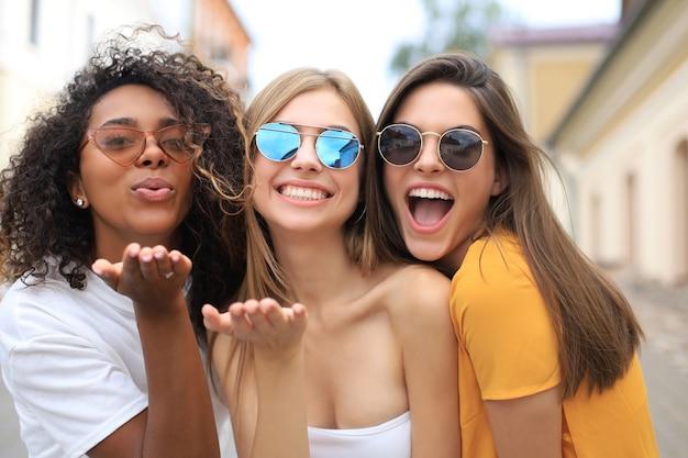 Três mulheres de beleza vestindo roupas de verão, posando juntas na cidade e olhando para a câmera, mandando um beijo.