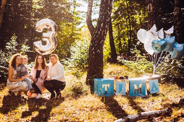Três mulheres e um menino sentam-se com balão de prata