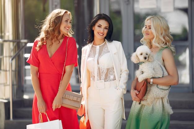 Três mulheres elegantes com sacolas de compras em uma cidade