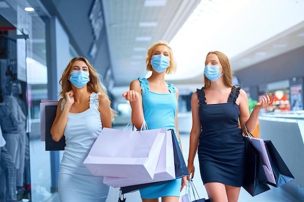Três mulheres elegantes em máscara médica protetora segurando sacolas de compras depois de fazer compras no ...