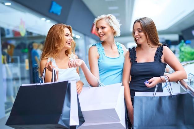 Três mulheres elegantes segurando sacolas de compras após a liquidação do consumismo negra sexta-feira