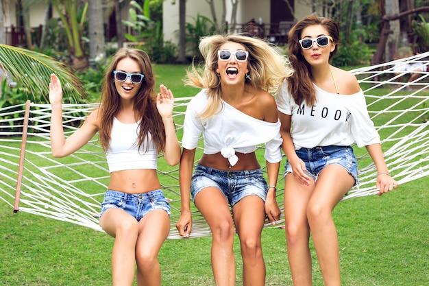 Três mulheres em forma incrível com pernas longas e sensuais posando em um jardim tropical, usando miniescurtos da moda e tops brancos simples