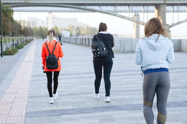Três mulheres em roupas esportivas caminham ao longo da calçada de um parque da cidade no verão. ð'ack view.