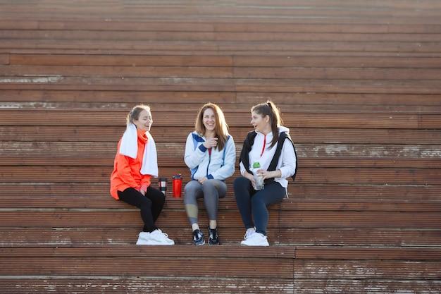 Três mulheres em roupas esportivas depois de um treino sentado nos degraus de madeira em um parque da cidade de verão. pôr do sol. luz de fundo.