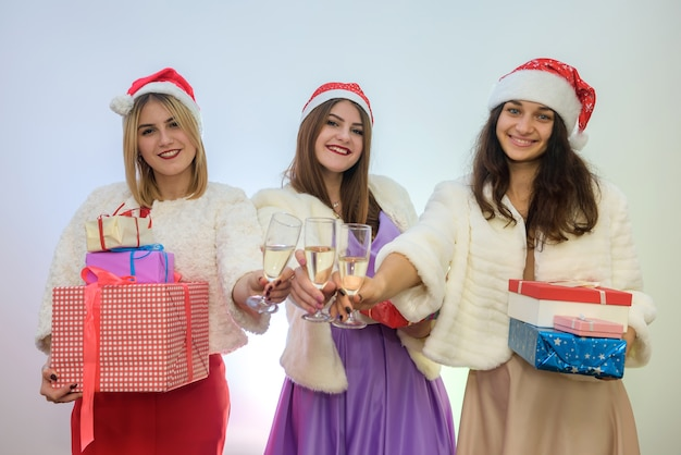 Três mulheres em vestidos elegantes e gorros com taças de champanhe. conceito de feliz natal.