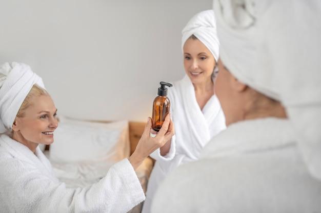 Três mulheres encantadas olhando para um produto cosmético