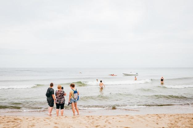 Três mulheres estão na praia e tiram fotos dele no telefone