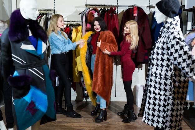 Três mulheres experimentando um casaco de pele na loja