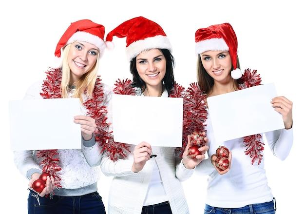 Três mulheres fantasiadas de papai noel com pôsteres em branco