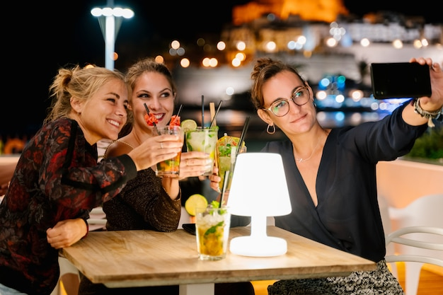 Três mulheres fazendo uma selfie enquanto está sentado no terraço, beber cocktails à noite