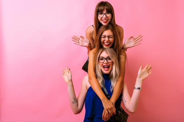 Três mulheres felizes se abraçando e se divertindo juntas