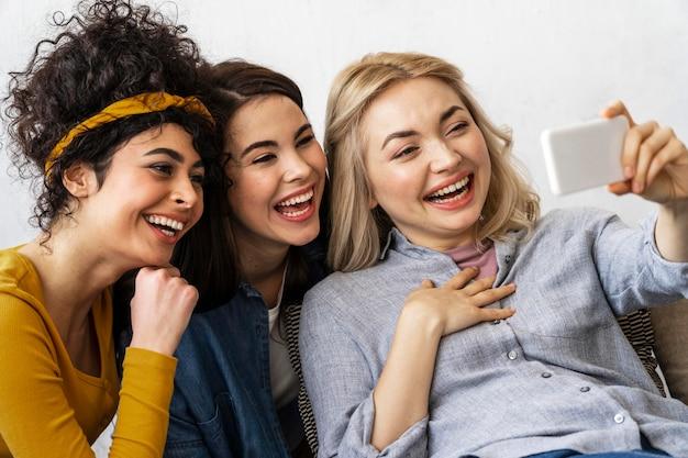 Três mulheres felizes sorrindo e tirando uma selfie