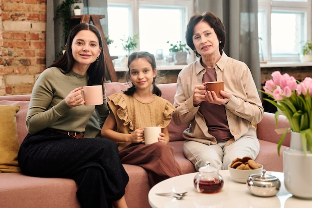 Três mulheres felizes tomando chá enquanto estão sentadas no sofá ao lado da mesa servida