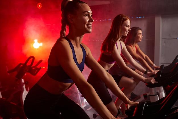 Três mulheres gostam de malhar na bicicleta ergométrica na academia, treino cardio intenso na academia. conceito de esporte e estilo de vida saudável