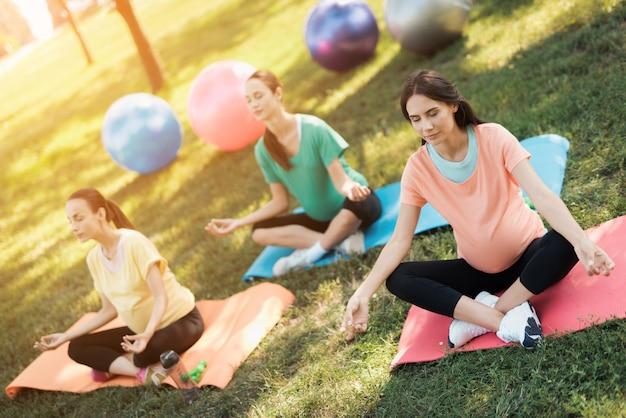 Três mulheres gravidas sentam-se em esteiras da ioga em uma pose dos lótus.
