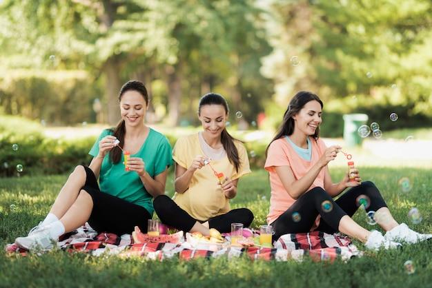 Três mulheres gravidas sentam-se em um parque e sopram bolhas.