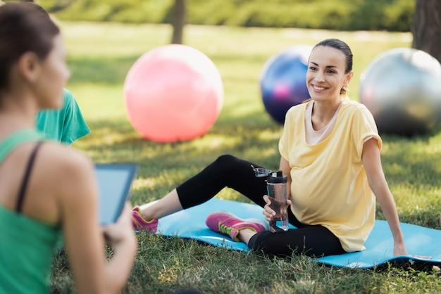Três mulheres grávidas vieram para a aula de yoga.